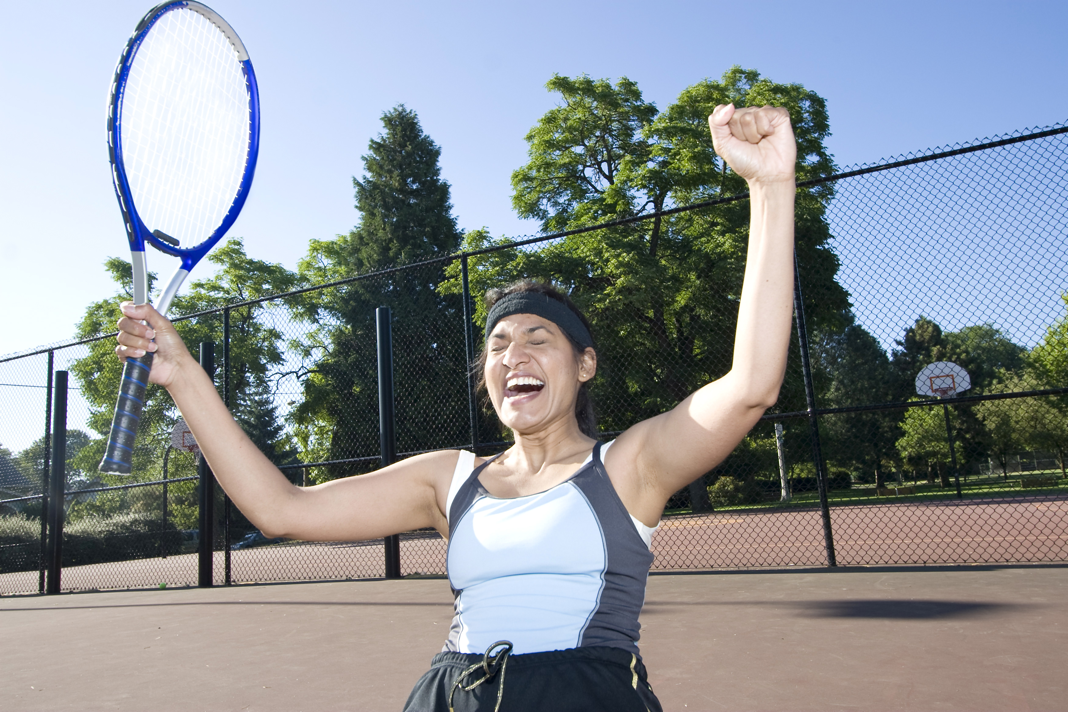 Tennis Player Smiling With Hands Up In Celebration. Horizontal